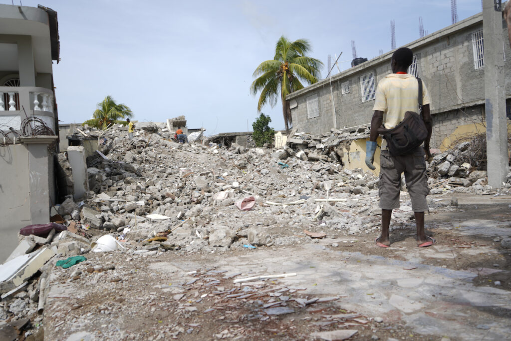 Man stares at rubble of a building caused by 2021 Haiti earthquake