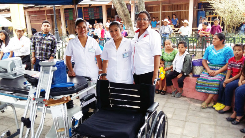 Health workers smiling behind the equipment donated to the health services of Uspantán, Guatemala