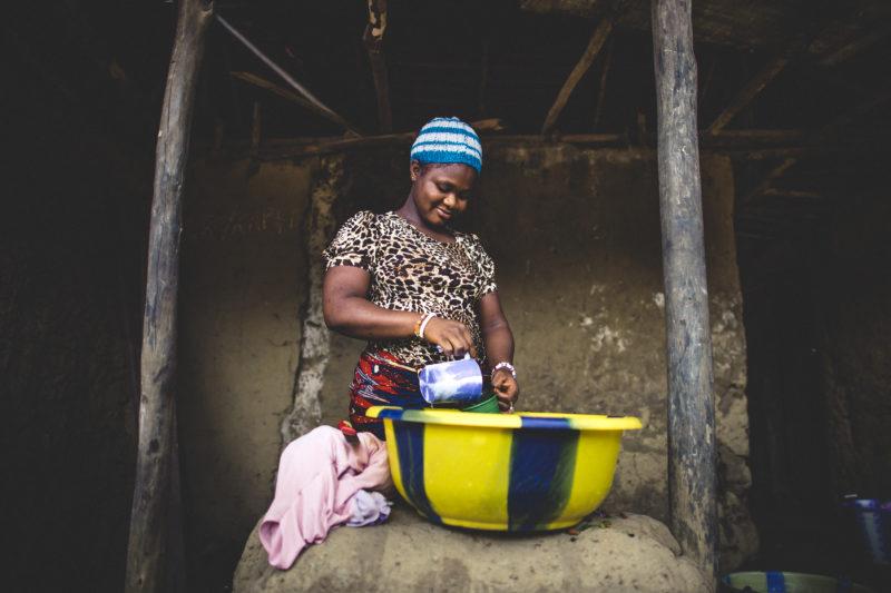 Assatu's, a resident in Liberia, doing housework in her home