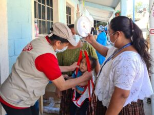 Guatemala, Hurricane Response, Medical Teams staff measure baby's weight at shelters where families are staying