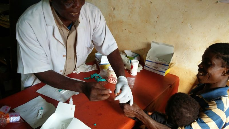 A health worker tests a child for malaria with a Malaria Rapid Diagnostic Test