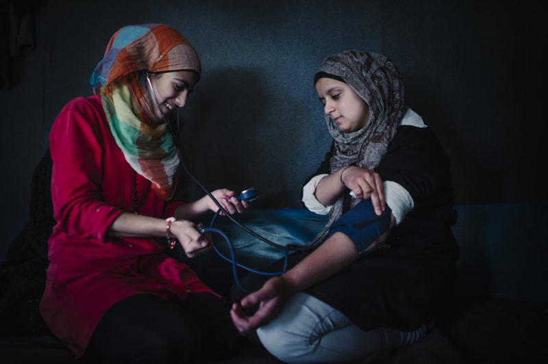 A community health worker take the blood pressure of another refugee woman
