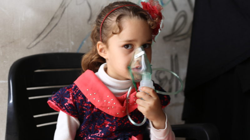 A Syrian girl receives oxygen at a health clinic