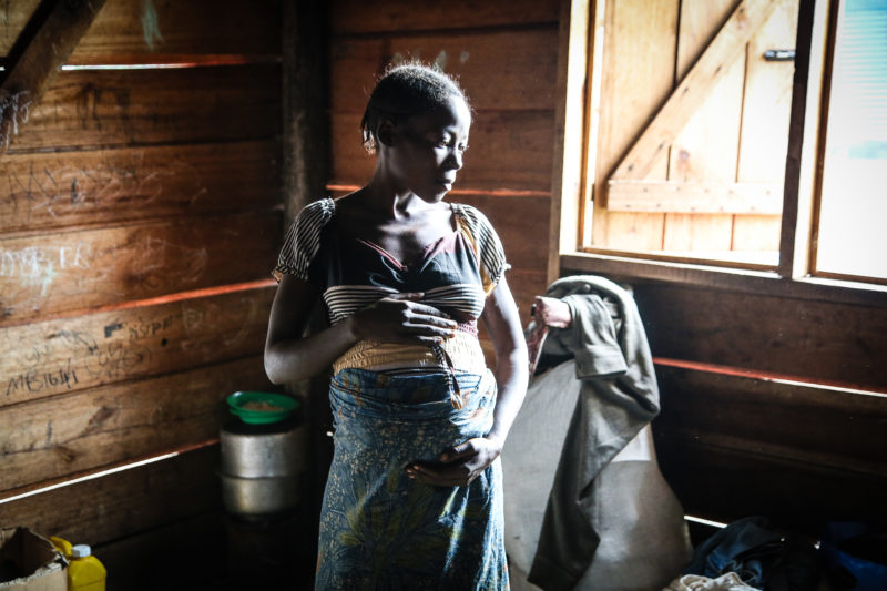 Mama Myombi cradling her pregnant belly in a refugee shelter