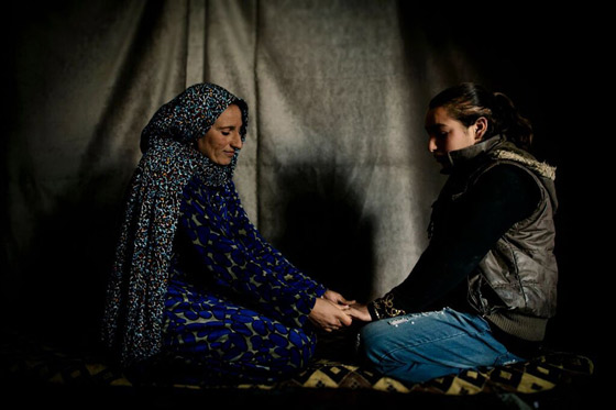 Amal and Abir, a mother and daughter, holding hands inside their tent in the Syrian refugee settlement