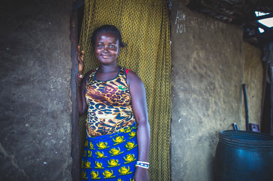 Kadiatu, a resident in Liberia's, smiling and standing at the door of her home