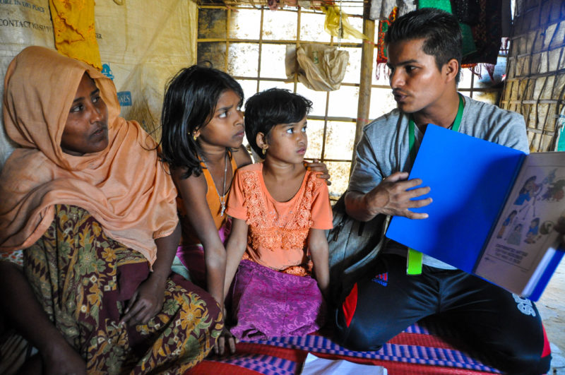 Fatema, a rohingya refugee woman, listens to Redwan, a Medical Teams International community health worker