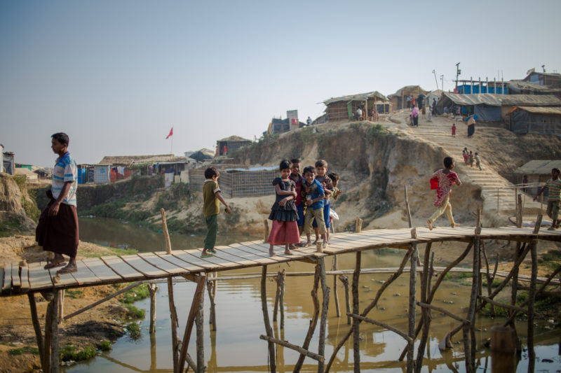 Rohingya refugee kid's on top of a bridge over the river need low-lying homes in Bangladesh