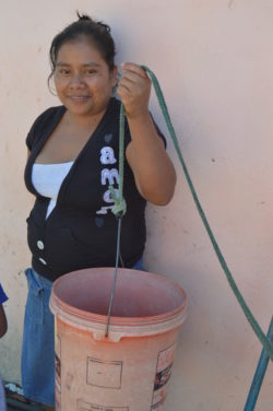 Juana, a local Guatemalan, holding a bucket she used to fill with water and pull up from her previous water system