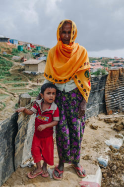 Amina and her grandson stand on muddy embankment in the Kutupalong refugee camp in Bangladesh