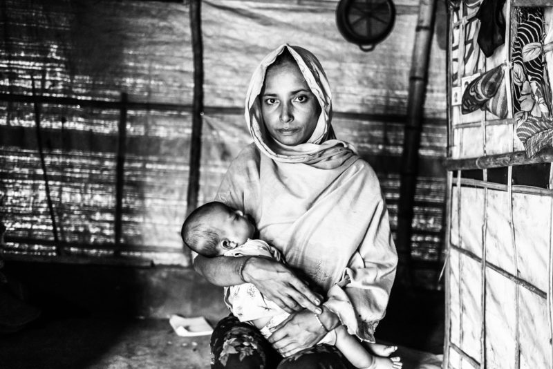 Gul Meher, a Rohingya refugee woman, holding her daughter Shorifa in a Bangladesh refugee camp