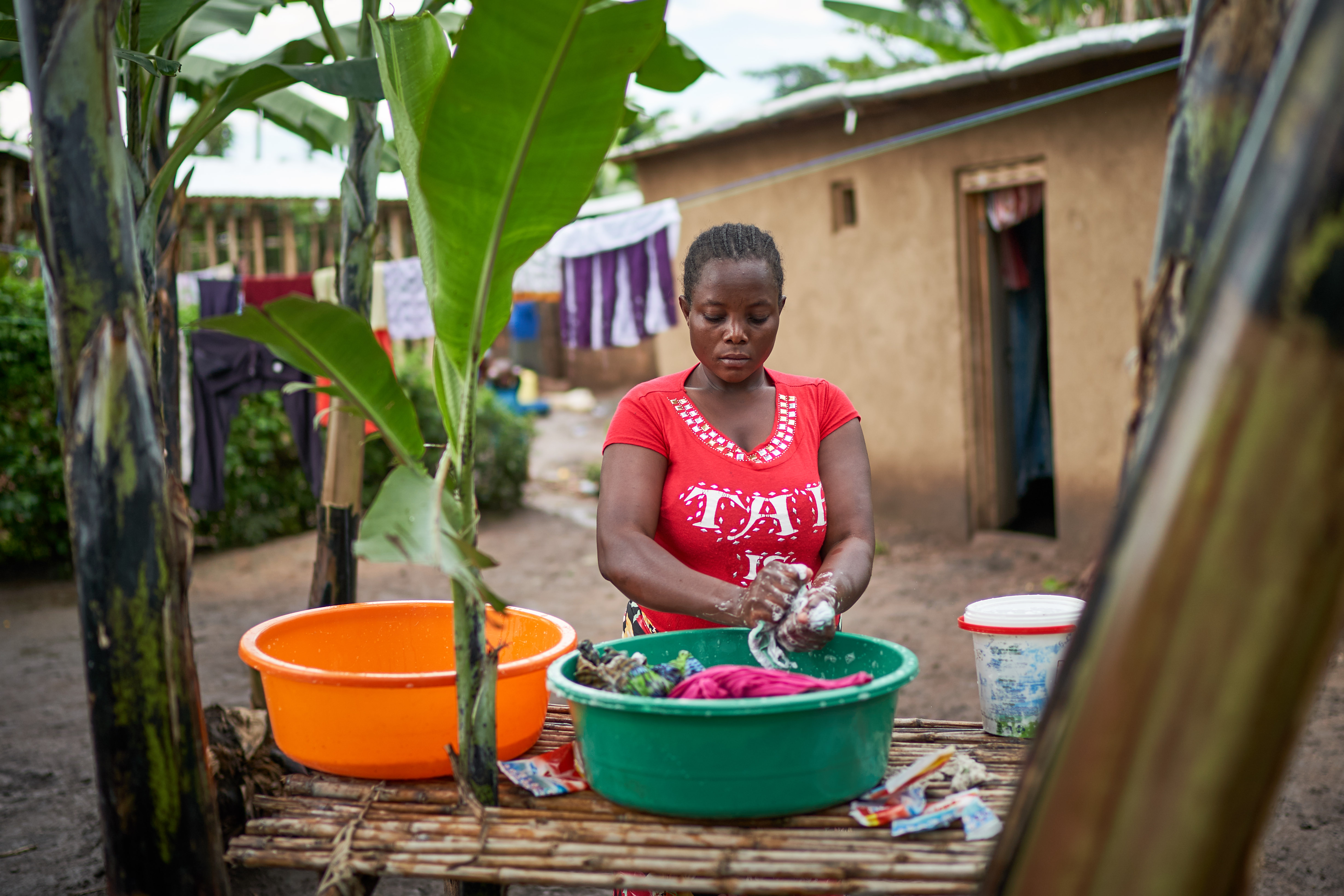 Janet washes clothes outside her home in Kyangwali refugee settlement in Uganda