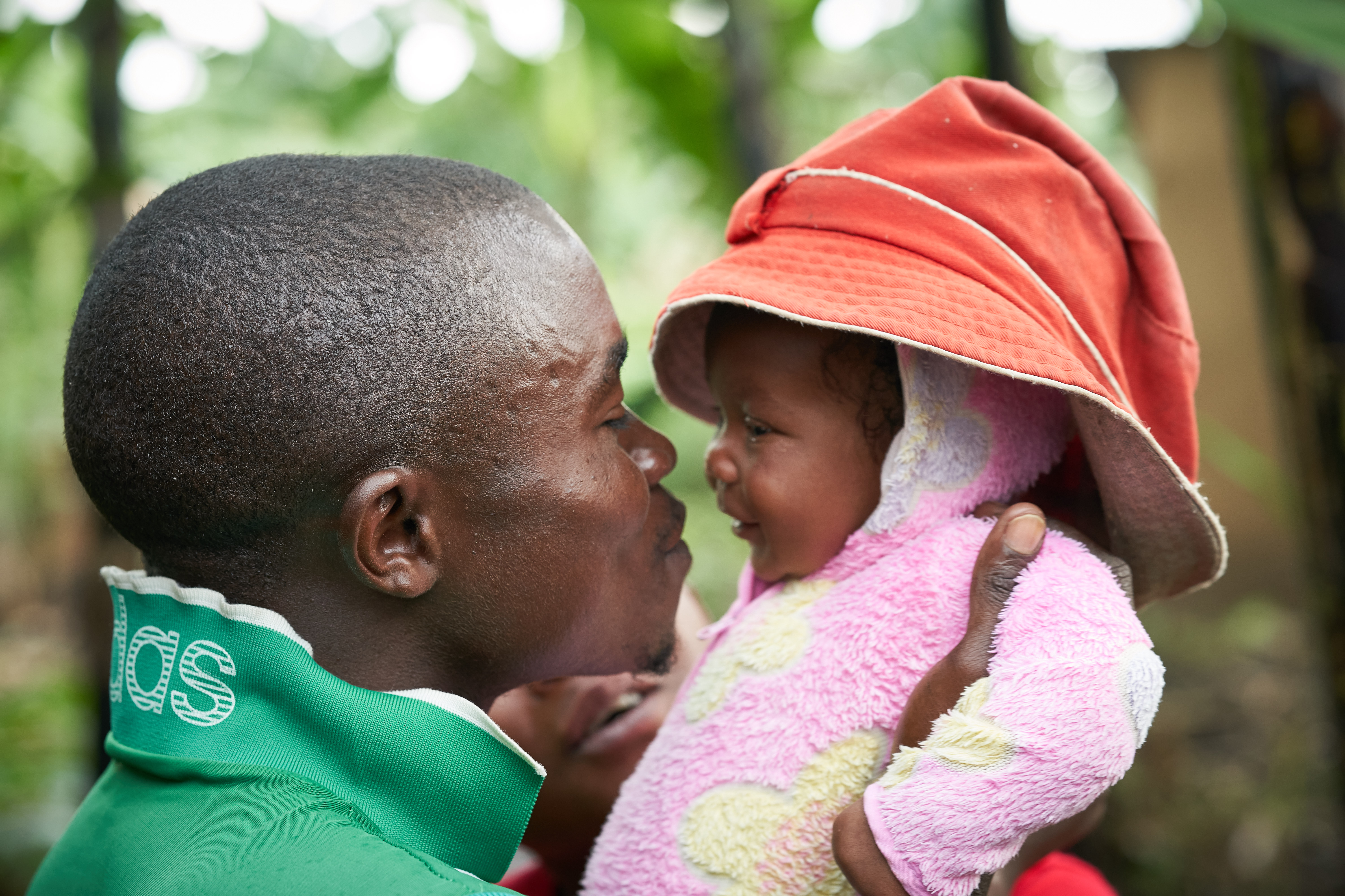 Gallas, Janet's husband and Uganda refugee, holding his daughter Vanessa