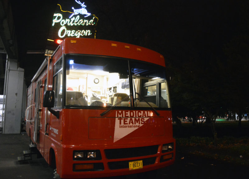 Mobile Dental van parked in front the Portland Oregon White Stag Sign