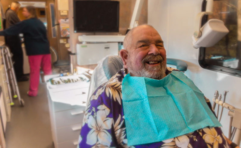 Joe, a smiling patient waiting to get his tooth extracted in the mobile dental clinic