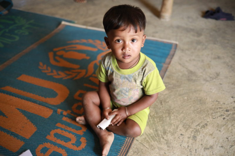 Salamot, a Bangladesh refugee boy, sitting on the floor of a health clinic to receive a vaccination