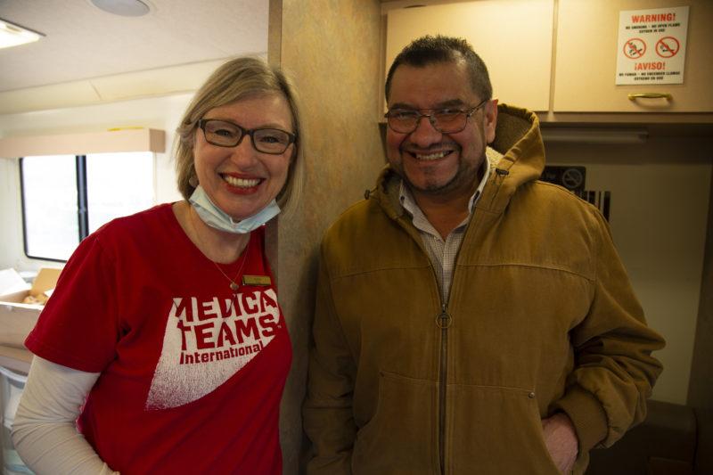 Alberto smiles with volunteer, Kathi, after being treated on board the mobile dental van