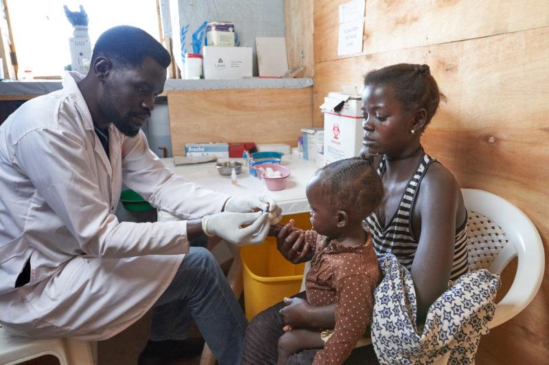 A Medical Teams health worker screens for disease at Kyangwali settlement, Uganda