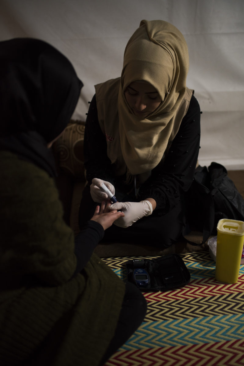 Shaza, the Senior Refugee Outreach Volunteer, giving medical care to a child with diabetes in a Lebanon refugee camp