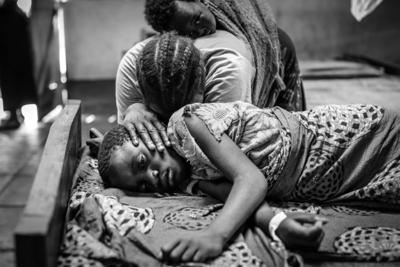 Kentia, a 9-year-old refugee in Tanzania, laying in the hospital bed as her mother mourns over her severe case of malaria