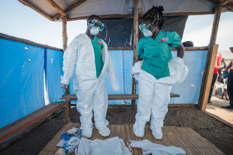 Medical Teams staff puts on protective clothing before screening newly-arrived refugees for Ebola