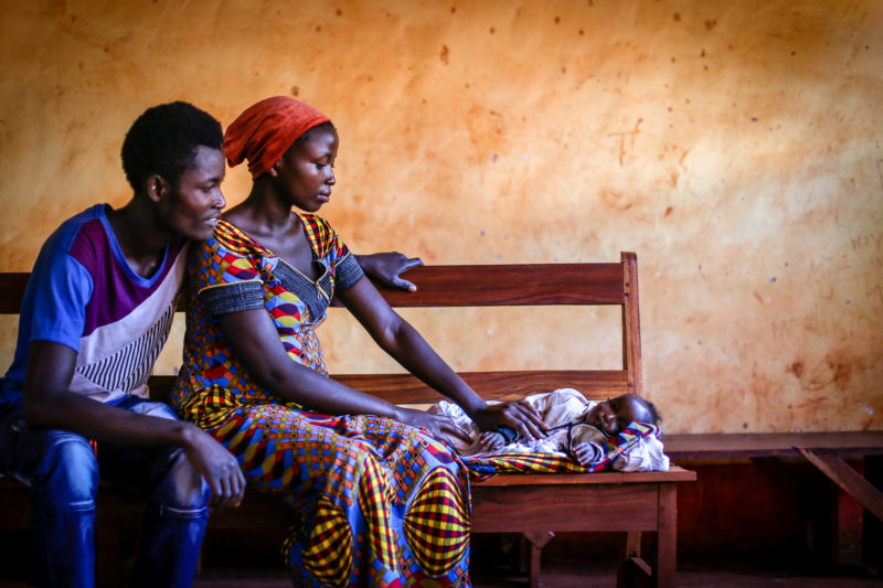 •Fidel and Adella, a young Nyarugusu refugee couple, looking at their newborn child sleep