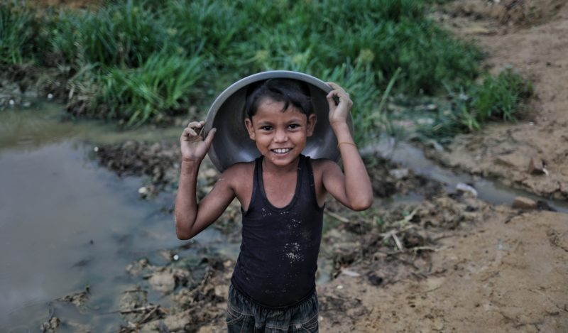 •A Rohingya boy covers himself from the rain in Bangladesh during monsoon season
