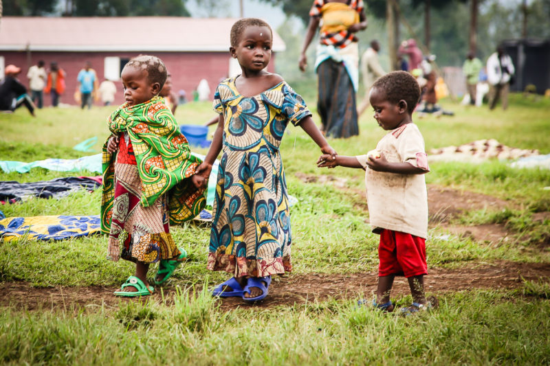 Three Uganda refugee children holding hands in a field of the health centers