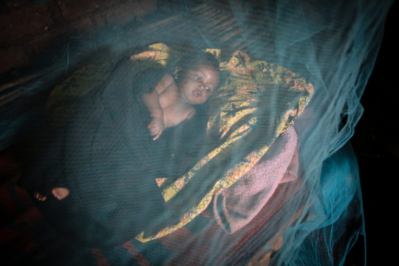 •Rwamba lays under a bed net, a donated medical supply, to protect him from malaria-carrying mosquitoes