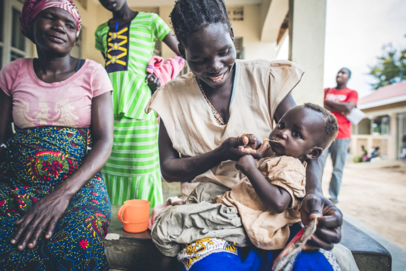 A smiling refugee woman feeding supplemental food to her baby, Brenda