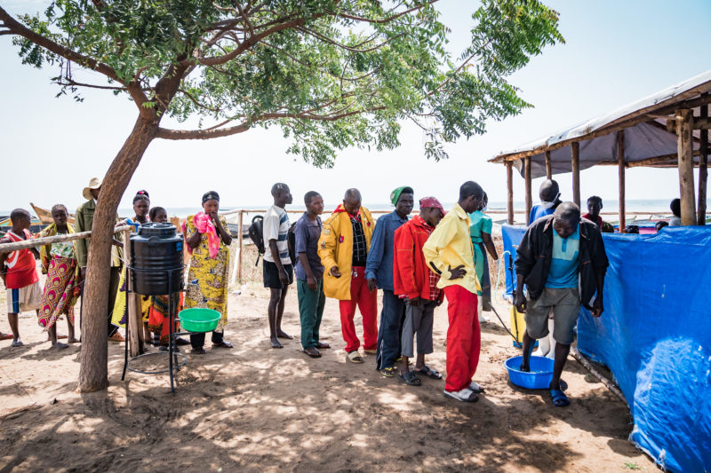 •Congolese refugees standing in line to be screened for Ebola before entering camp