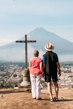 A man and a woman hold hands while looking toward a cross and volcano in Antigua, Guatemala