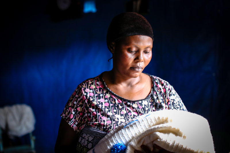 Suzanne, looking down at a blanket that once was her 5-month-olds, who had died from malaria