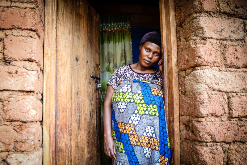 Suzanne, a refugee in the Nyarugusu camp, standing in the doorway of her home in Tanzania