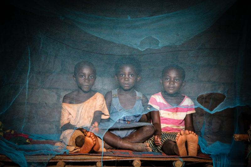 Three of Suzanne's children, sitting underneath their damaged mosquito nets that are suppose to protect them from malaria