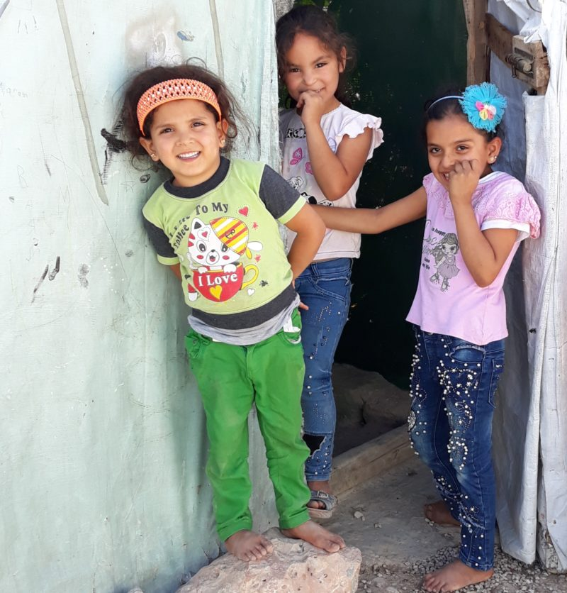 Syrian Refugee girls laughing in the doorway of their home in Lebanon