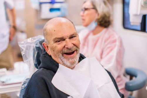 Tim, a visitor at a Mobile Dental Clinic, sitting in a chair smiling with a teeth less grin