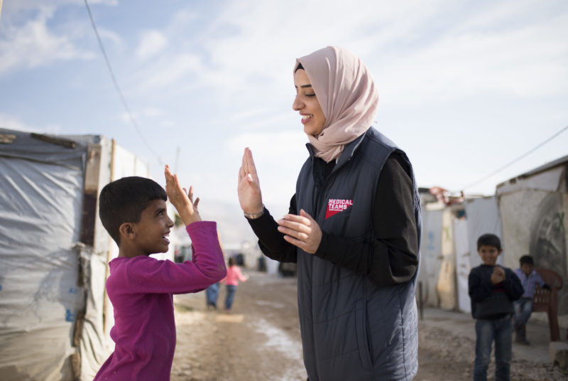 Shaza, a community health worker in Lebanon, high-fives a Syrian refugee girl