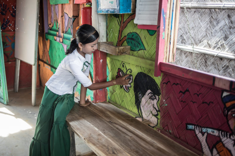 Maisara, one of the Rohingya refugee girls, showing her art from art therapy