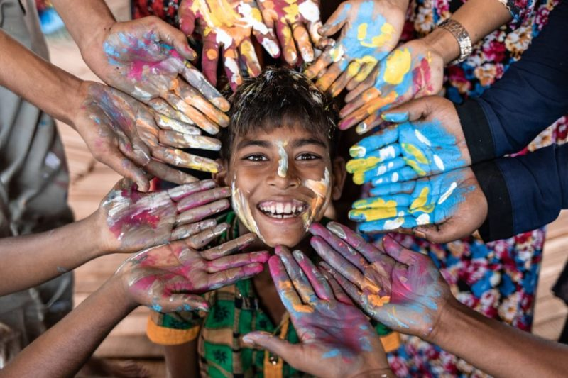 A Rohingya refugee boy covered in paint and smiling, with painted hands surrounding his face