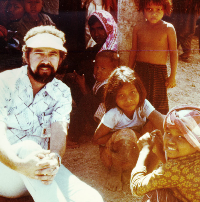 Ron Post, founder of Medical Teams International, sits with Cambodian refugees