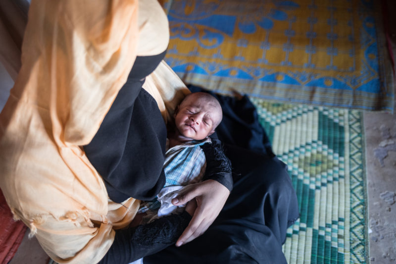 Tasmin Ara, a refugee in Bangladesh, holding her newborn baby girl