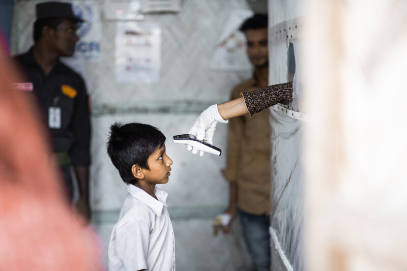 A young refugee boy in Bangladesh is scanned with an infrared thermometer in the Isolation and Treatment Center for COVID-19.