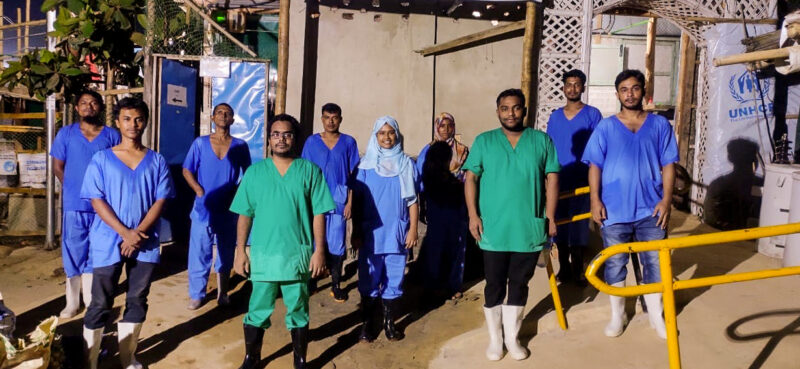 A team of ten health workers stand outside the isolation and treatment center in Bangladesh.