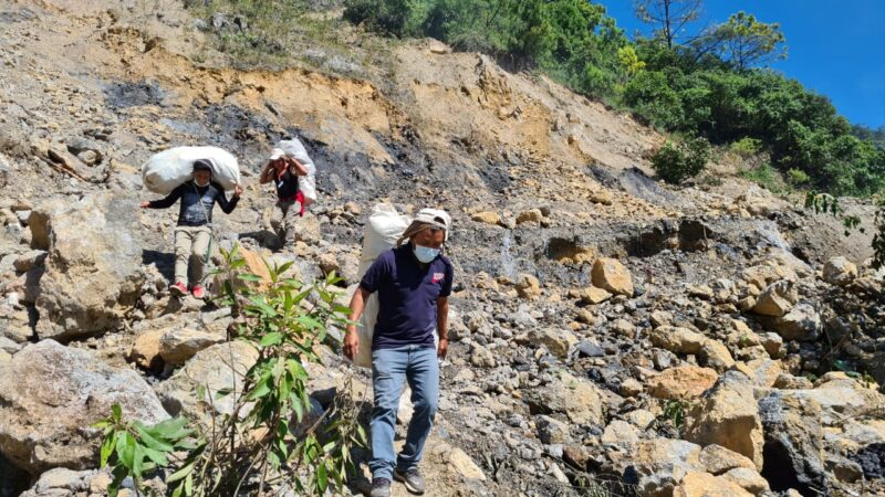 Staff members Celestino, Romeo and Carlos carry hygiene kits on foot to villages where the route was blocked by landslides.