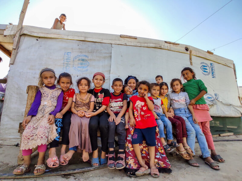 Mazen (center) with his cousins and siblings outside of his home in the refugee settlement in Lebanon.