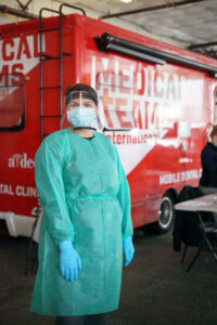 A Medical Teams volunteer in gown, gloves, mask, and face shield stands outside the van at a COVID testing clinic.