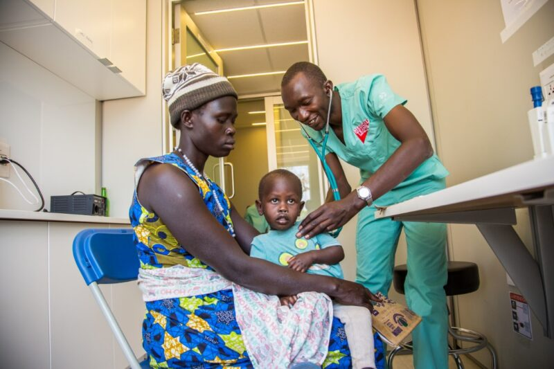 Inside a mobile medical container a doctor examines a child patient, Adjumani, Uganda.