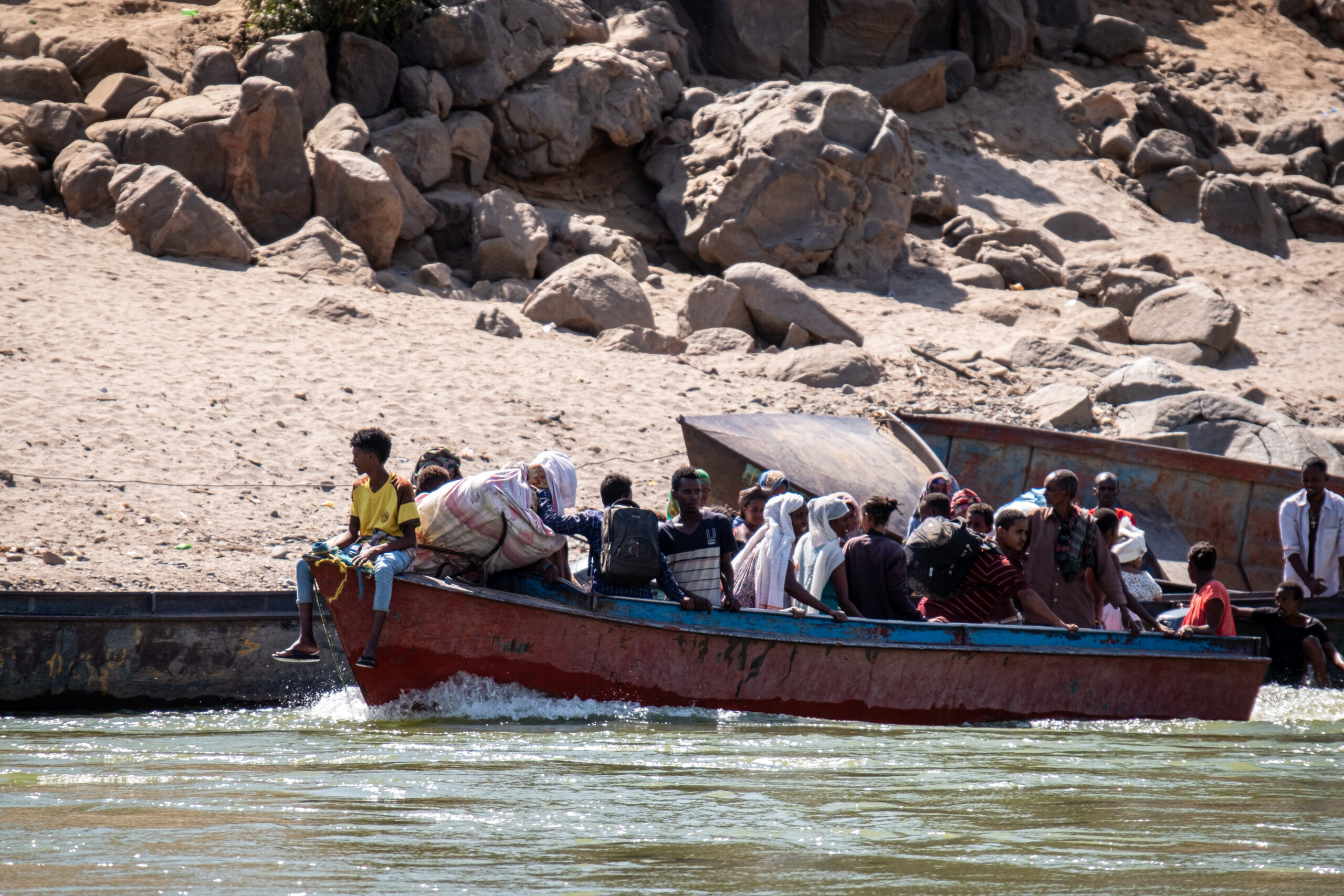 Ethiopian refugees crossing the Tekeze River in a boat. Photo by Joost Bastmeijer.