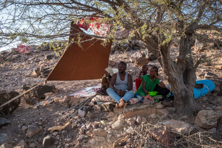 A family sits under a makeshift tent and tree, Ethiopian refugees in transit. Photo by Joost Bastmeijer.